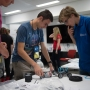 A group of students gather around a robotic car. Image courtesy of T8 Photography