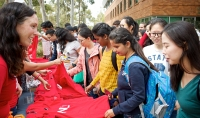 Students selecting free red ANU t-shirts at the 2018 Welcome Party